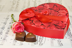 Heart box of chocolates with rose over music notes