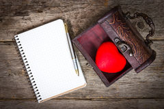 Heart in the  box and notebook with a pen Stock Image
