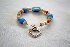 Heart bracelet. Bracelet with blue beads and a big silver heart Royalty Free Stock Photo