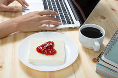 Heart on bread, made of strawberry jam. And hand typing on laptop Royalty Free Stock Photo