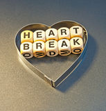 Heart break. Text ' heart break ' in black upper case letters on small white cubes placed inside a silver heart shape on a gray background Royalty Free Stock Image