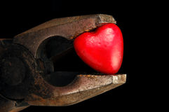 Heart breaker. Heart squeezed by rusty tool Royalty Free Stock Image
