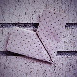 Heart on a brick wall. An origami heart on a brick wall with a retro effect Stock Image
