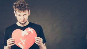 Sad man with glued heart by plaster. Heart broken concept. Unhappy sad man guy holding glued on love sign symbol. Human feeling repared by plaster. Valentines Royalty Free Stock Photos