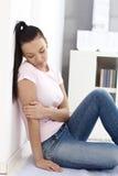 Heart-broken kvinna som hemma sitter på golv fotografering för bildbyråer