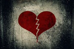 Heart broken painted on grunge cement wall background - love con Stock Photos