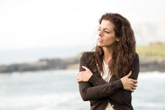 Heart broken sad woman. Sad shivery woman in brown sweater jacket hugging herself on late summer cold day in coast landscape. Sadness, melancholia and heart Royalty Free Stock Images