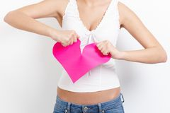 Heart-broken woman tearing paper heart royalty free stock photography