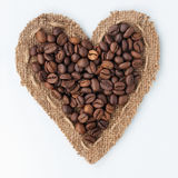 Heart of burlap and coffee beans lying on a white background. Can be used as texture Stock Photography