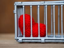 Heart in the cage Put on a wooden table, It shows the closure of freedom and love. Love is disappointed and not satisfied. Closing. And blocking in love Royalty Free Stock Photo