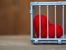 Heart in the cage Put on a wooden table, It shows the closure of freedom and love. Love is disappointed and not satisfied. Closing. And blocking in love Royalty Free Stock Image