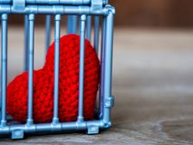 Heart in the cage Put on a wooden table, It shows the closure of freedom and love. Love is disappointed and not satisfied. Closing. And blocking in love Royalty Free Stock Images