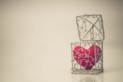 Heart in a cage. A cage with a red heart inside / Heart in a cage concept Stock Photo