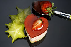 Heart cake. Heart shaped strawberry cake with carambola or star fruit decoration over black background Stock Images