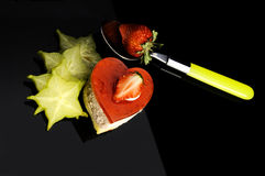 Heart cake. Heart shaped strawberry cake with carambola or star fruit decoration over black background Stock Photos