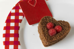 Heart of cake and raspberries, red card Stock Photos