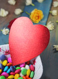 Heart on candies. Heart with candies in a bowl on the wooden background royalty free stock image