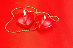 Heart of a candle with a necklace on a red silk Stock Photography