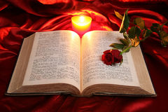 Heart candle on open Bible and red rose Royalty Free Stock Photos