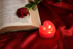 Heart candle on open Bible and red rose Royalty Free Stock Image