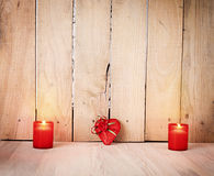 Heart candle. Two candles and a wrapped heart shaped gift on wooden background Stock Image