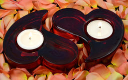Heart candles like a love symbol. Heart shape candles in roses flakes Stock Images