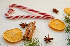 Heart of candy cones on the white table with traditional spices anise stars, cinnamon sticks, dried oranges. New year food Royalty Free Stock Images