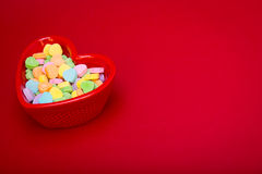 Heart Candy Dish Left. A heart shaped candy dish filled with heart candies left justified on a red textured background. copyspace stock photography