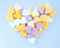 Heart from candy hearts on blue background. Heart made from sweet colorful candy hearts on blue background Stock Photography