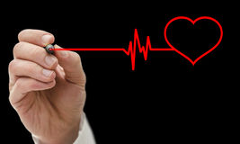 Heart care concept. Doctor drawing shape of a heart beating cardiograph. Isolated over black background stock images