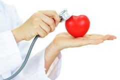 Heart care. Doctor holding heart in hands with stethoscope, heart care concept Stock Photos