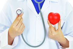 Heart care. Doctor holding heart in hands with stethoscope, heart care concept Stock Images