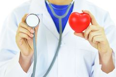 Heart care. Doctor holding heart in hands with stethoscope, heart care concept Stock Photo