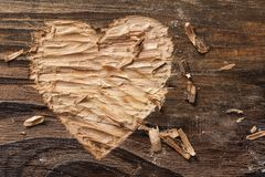 Heart carved. Into wooden plank stock photo