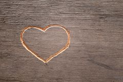 Heart carved on the wooden plank. Cuttings from wood. Valentine`s Day. A symbol of love. A pattern on the tree royalty free stock image