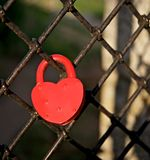 The heart of the castle. Red heart-shaped lock mounted in love on the fence of the park. It is a sign of eternal love and respect Stock Photography