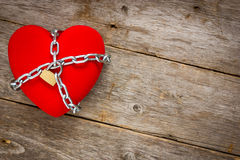 Heart with chains on wooden background Stock Images