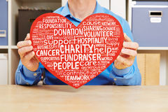 Heart with charity and fundraiser tag cloud. Man holding big red heart with charity and fundraiser tag cloud against cancer Stock Image