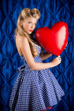 From the heart. Charming pin-up woman with retro hairstyle and make-up holding red balloon in the shape of heart Royalty Free Stock Images