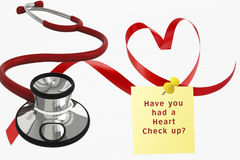 Heart Check Up. Red Stethoscope and a ribbon shaped in the shape of a heart with a yellow sticky note. Concept of going to the doctor for a heart checkup and stock photography