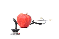 Heart Checkup. Stethoscope and red apple isolated on white background Royalty Free Stock Images
