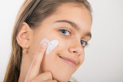 Heart on the cheek. Portrait of young girl applying cream on her pretty face. girl with cream on her cheek Royalty Free Stock Photos