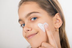 Heart on the cheek. Portrait of young girl applying cream on her pretty face. girl with cream on her cheek Stock Images