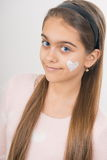 Heart on the cheek. Portrait of young girl applying cream on her pretty face. girl with cream on her cheek Royalty Free Stock Images
