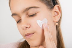Heart on the cheek. Portrait of young girl applying cream on her pretty face. girl with cream on her cheek Royalty Free Stock Photography