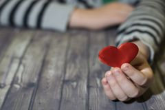 Heart in child hands. Wooden background. A child holds a heart in his hands. Valentines Day. stock photo