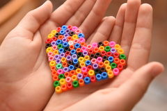 Heart in child's hands. Heart made of hama beads in child's hands closeup Royalty Free Stock Photos