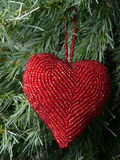 Heart and christmas. An heart decoration for christmas with a tree on the background Royalty Free Stock Images