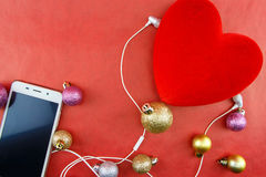 Heart with christmas ornaments and smartphone with earphones, on red Royalty Free Stock Photo
