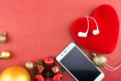 Heart with christmas ornaments and smartphone with earphones, on red Stock Photography
